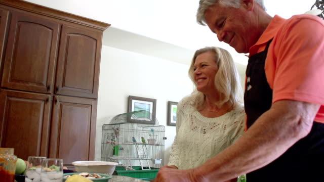 vídeos de stock e filmes b-roll de câmara lenta-divertido amadureça preparar alimentos na cozinha. - jovem de espírito