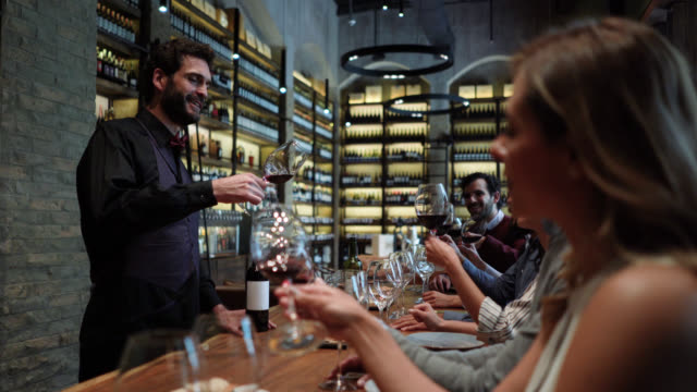 a fun night for couples tasting wine following male sommelier - wine bar stock videos & royalty-free footage