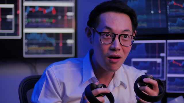 fun of asian businessmen age 34 yearold holding controllers plays in a video game at home of working late while computer monitors showing line graphs about business investment on back.screen time - watching tv and gaming concept. - game night leisure activity stock videos & royalty-free footage