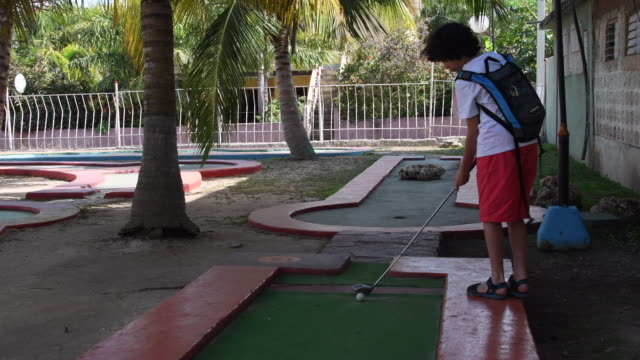 a fun place for everyone where you can enjoy a challenging and exciting miniature golf course this is the largest minigolf in varadero there's a... - solo un bambino maschio video stock e b–roll