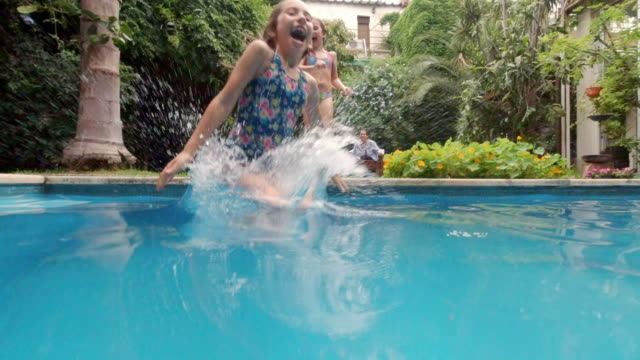fun sisters jumping into family swimming pool - swimwear stock videos & royalty-free footage