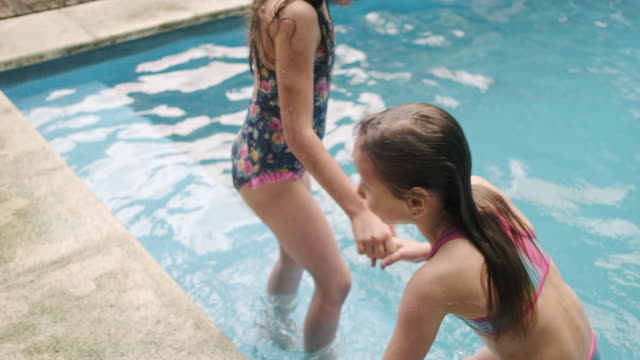 fun sisters swimming in family swimming pool - swimwear stock videos & royalty-free footage