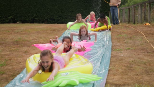 fun with inflatables - water slide stock videos & royalty-free footage