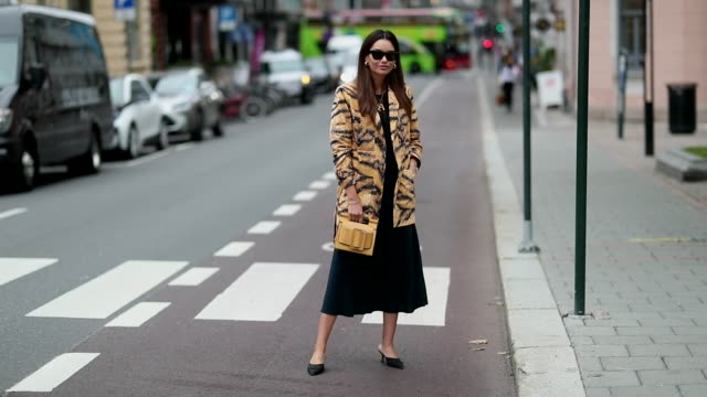 Funda Christophersen wearing a yellow bag dress and a coat with animal print tiger is seen outside the 'Moire' show during Oslo Runway SS19 on August...