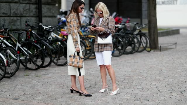 Funda Christophersen wearing checked Burberry button shirt and white midi skirt black heels Prada sunglasses seen outside the Cathrine Hammel show...