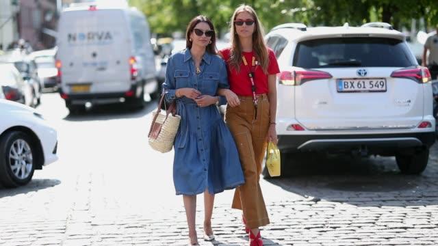 Funda Christophersen wearing denim dress Loewe bag and Trine Kjaer wearing red tshirt brown pants yellow Balenciaga triangle bag seen outside...