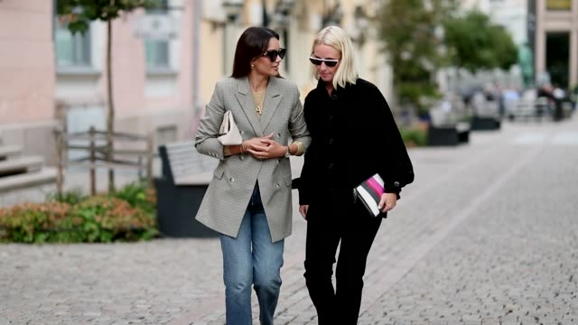 Funda Christophersen wearing denim jeans and a grey blazer and a guest wearing black jacket and pants are seen outside the 'Michael Olestad' show...