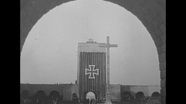 vidéos et rushes de [8/9/34] ws funeral ceremony at the outdoor tannenberg memorial / pov through arch of christian cross with iron cross emblem in background / [1934]... - 1934