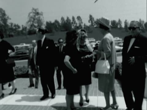funeral for wild animal trainer, actor and entertainer clyde beatty / entertainer emmett kelly sr. wearing sunglasses while walking toward church /... - モンタージュ・ビバリーヒルズ点の映像素材/bロール