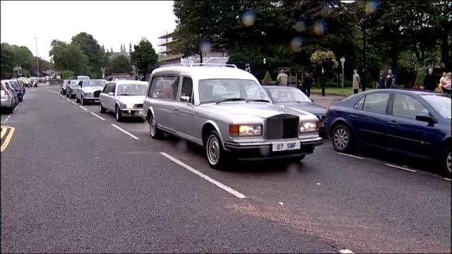funeral of liberal politician cyril smith ext / raining funeral cortege along / hearse containing coffin of cyril smith along past / people standing... - cyril smith politician stock videos & royalty-free footage