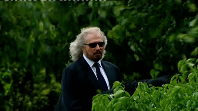 EXT BV Robin Gibb's coffin carried into church with photographers following Barry Gibb standing by graveside as he looks up to the skies PULL Uri...