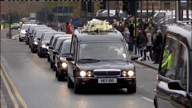 funeral of sir jimmy savile; england: leeds: ext pallbearers carrying gold coffin of sir jimmy savile from hotel to hearse hearse convoy along road... - mourner stock videos & royalty-free footage