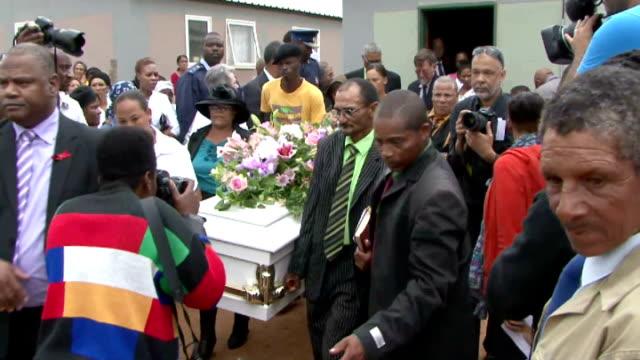 funeral of teenager gang raped and murdered; **music heard sot** people carrying coffin towards - チンピラ点の映像素材/bロール