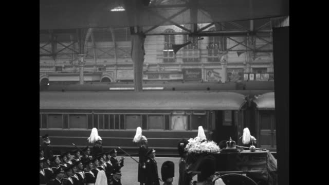 ws funeral procession marches solemnly into paddington station / vs coffin on caisson adorned by royal standard flowers crown scepter and orb... - queen dowager stock videos & royalty-free footage