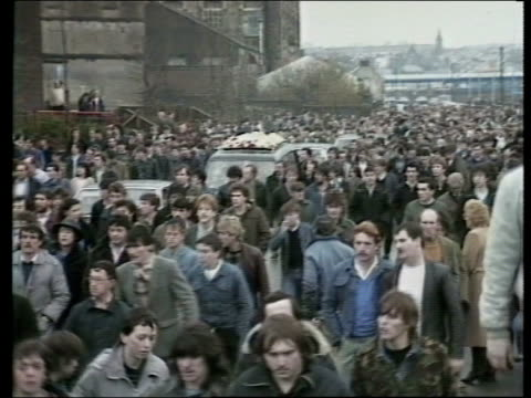 vídeos de stock, filmes e b-roll de londonderry ts ira supporters and police scuffle pan lr ts coffin of william fleming carried rl gv mass of ira supporters towards ms gerry adams sinn... - gorro