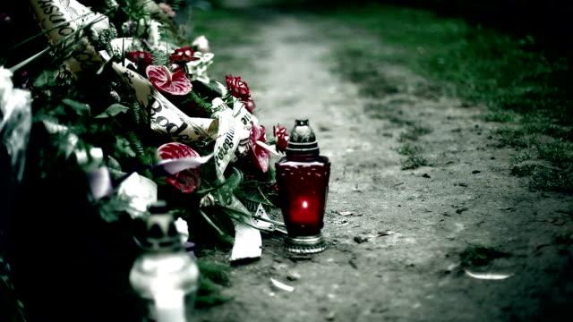 Begrafenis, krans en kaars op het graf