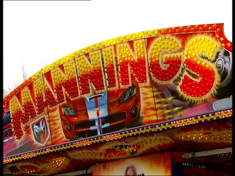 funfair in london's hyde park; england: london: hyde park: ext fun fair rides installed in park; 'mannings' sign on fairground ride; happy tea cups... - fairground stall stock videos & royalty-free footage