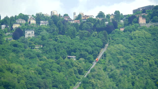vidéos et rushes de a funicular cable car goes up the hill on lake como, italy, europe. - slow motion - tramway