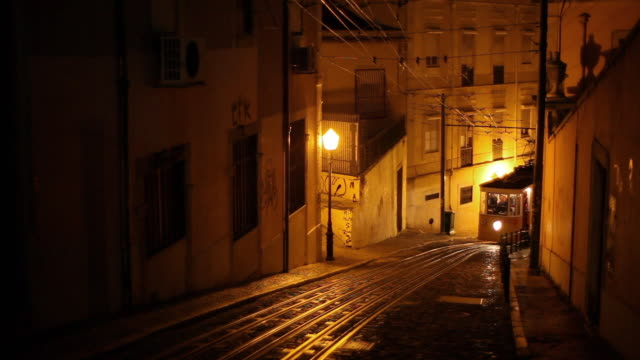 ws funicular elevador da gloria climbing up narrow street at night / lisbon, portugal - tram stock videos & royalty-free footage