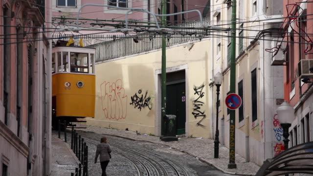 ws funicular elevador da gloria moving down narrow street / lisbon, portugal - 玉石点の映像素材/bロール
