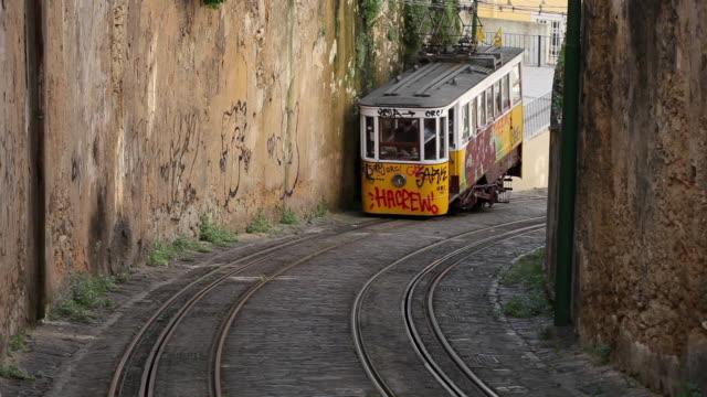 vídeos de stock, filmes e b-roll de ms cu funicular elevador do lavra climbing up narrow street / lisbon, portugal - bonde