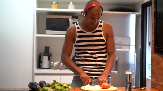 vídeos de stock e filmes b-roll de funny afro latin man dancing and cooking in kitchen at home - domestic kitchen