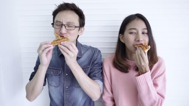 ピザを食べて面白いアジア カップル - unhealthy eating点の映像素材/bロール