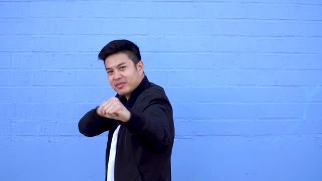 Lustige asiatische junge Mann tut Kung Fu geht.