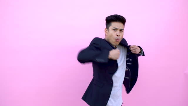 funny asian young man doing kung fu moves. - colored background stock videos & royalty-free footage