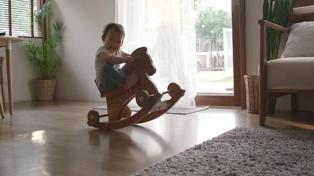 vídeos de stock, filmes e b-roll de babysitting engraçado no cavalo do brinquedo. retrato full-length de uma menina de sorriso encantadora pequena que desgasta uma camisa branca e as calças azuis que balanç no cavalo de madeira do brinquedo. - cadeira