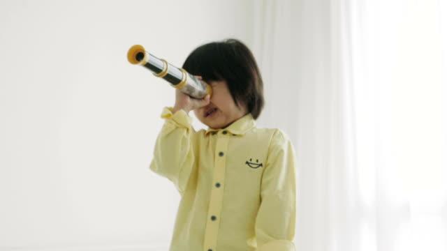 stockvideo's en b-roll-footage met grappige jongen met een verrekijker - verrekijker