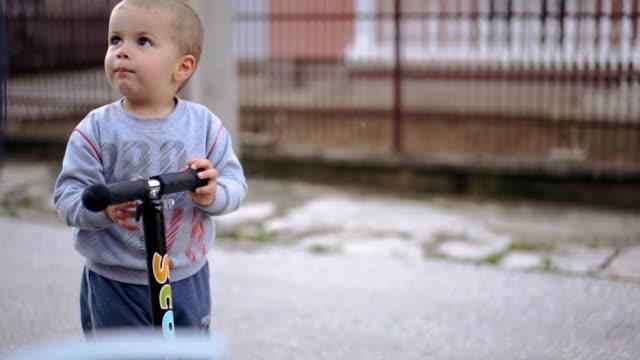 vidéos et rushes de garçon drôle avec le scooter - un seul bébé garçon