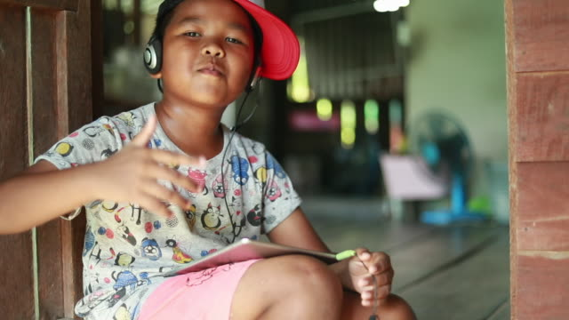 funny child in headphones listens to music hip hop, asian boy lifestyle, slow motion - singer stock videos & royalty-free footage