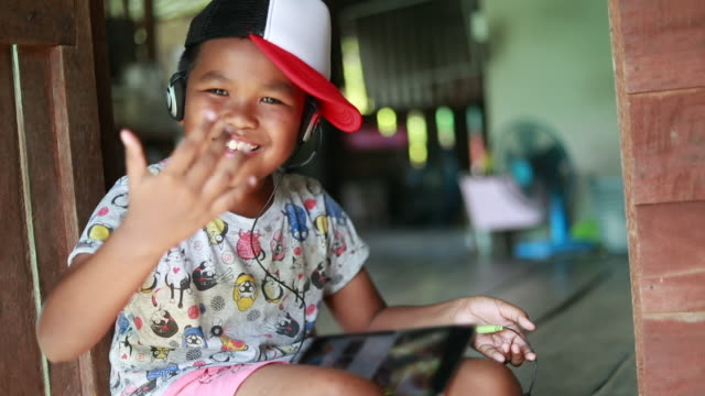 stockvideo's en b-roll-footage met funny child in koptelefoon luistert naar muziek hip hop, aziatische jongen lifestyle, slow motion - hiphop