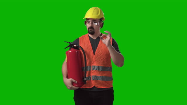 vídeos de stock e filmes b-roll de funny construction worker holding showing fire extinguisher chroma green screen background - bombeiro