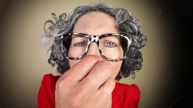 面白い魚眼古い女性は臭い何かを嗅ぐ - 悪臭点の映像素材/bロール