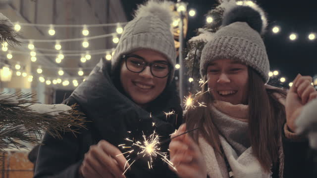 funny girls holding burning sparklers a new year celebration 4k resolution - human face video stock e b–roll