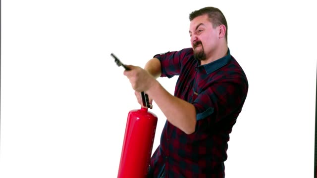 funny guy posing as a firefighter and pointing a fire extinguisher at imaginery fire - fire extinguisher stock videos & royalty-free footage