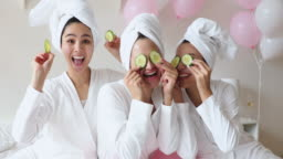 Funny happy asian women make cucumber mask having fun together