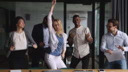 Funny happy diverse business team dancing together at corporate party
