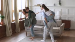 Funny happy parents carrying kids playing game in living room
