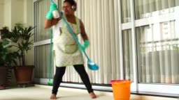 Funny Housekeeper Dancing and Having Fun With Broom