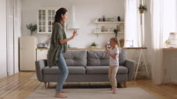 Funny kid daughter imitate mom dancing together in kitchen