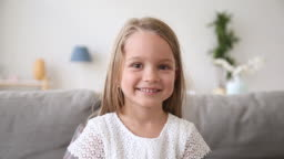 Funny little girl smiling looking at camera making video call