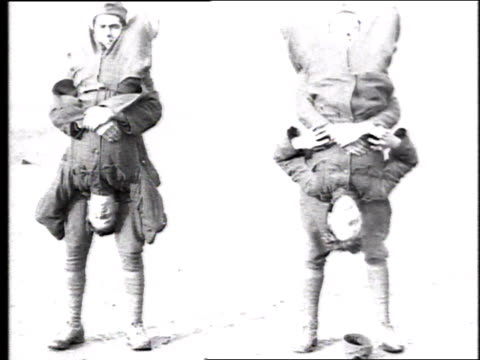 vídeos de stock e filmes b-roll de funny looking army drill has two soldiers lifting two others standing in front of them, turning them upside down so that soldiers' faces are at... - super exposto
