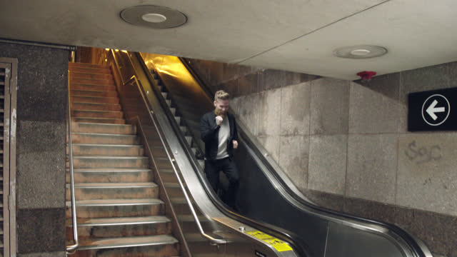 funny man jogs down escalator going the wrong way and smiles at camera in city subway. - ausrutscher stock-videos und b-roll-filmmaterial