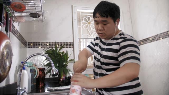 変な男が台所で音楽を聴く - 台所点の映像素材/bロール