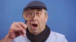 A funny mature man looks at the camera with a magnifying glass looking for valuable information.