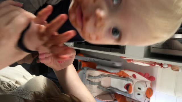 funny scene of a dad filming his son putting hands into a chocolate drink at home - vertical stock videos & royalty-free footage
