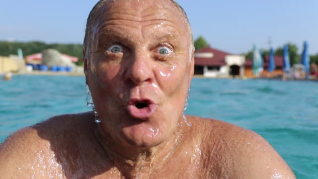 funny senior adult making faces in pool - active seniors stock videos & royalty-free footage
